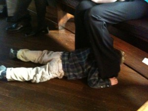 Hiding between my legs, under a pew